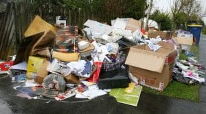 Household rubbish piled on the front yard and footpath waiting to be removed