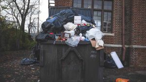 Large Waste Rubbish Bin Overflowing With Waste After De-Cluttering Home